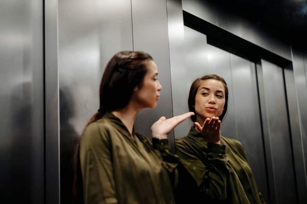 Kobieta przesyłająca buziaka do swojego odbicia w lustrze