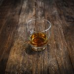 Szklanka alkoholu na drewnianym stole